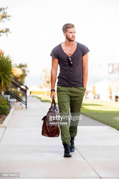 Caucasian man carrying suitcase on concrete sidewalk