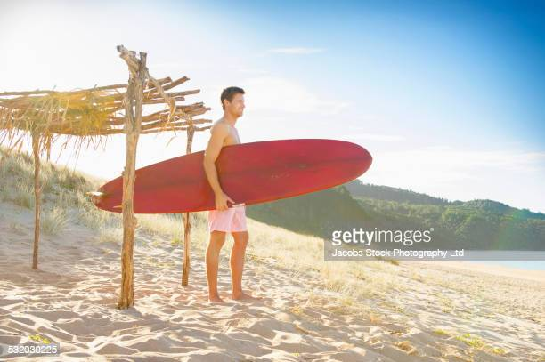 caucasian man carrying surfboard on beach - whangarei heads stock pictures, royalty-free photos & images