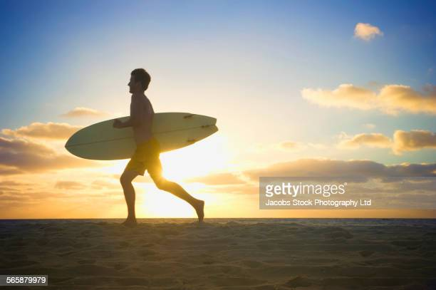Caucasian man carrying surfboard on beach