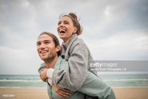 caucasian man carrying woman piggyback on beach - heterosexual couple photos - fotografias e filmes do acervo
