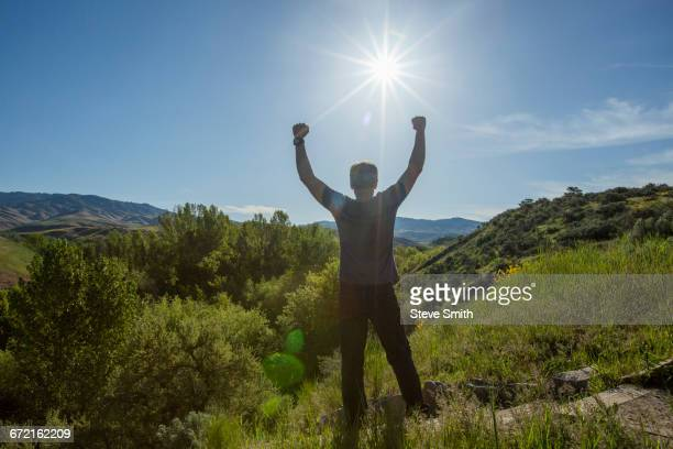 Caucasian man celebrating on mountain