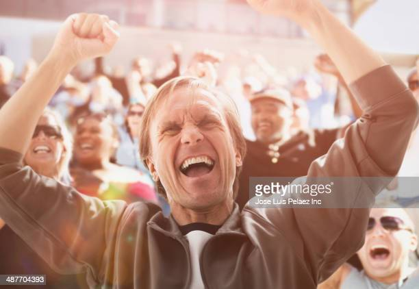 Caucasian man cheering at sporting event