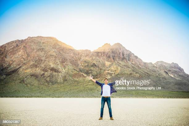 Caucasian man cheering in cracked desert landscape