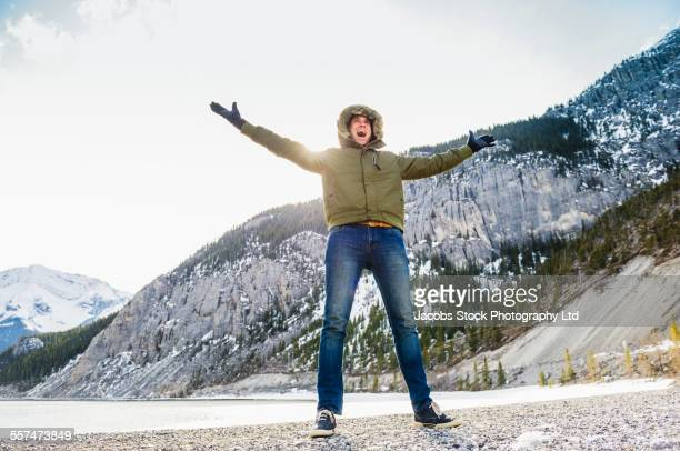 caucasian man cheering in snowy field - parka coat stock photos and pictures