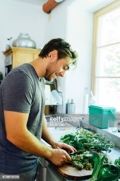 Caucasian man chopping vegetables in kitchen