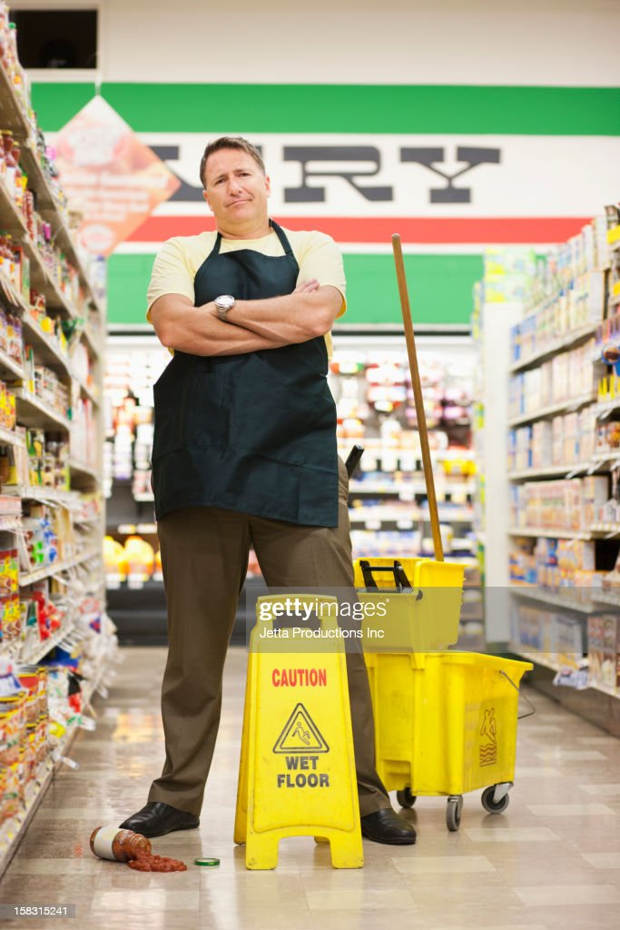 Caucasian man cleaning up spill in grocery store : Stock Photo