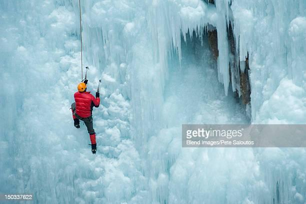Caucasian man climbing ice wall