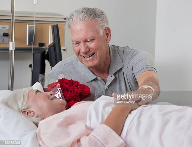 Caucasian man comforting wife in hospital