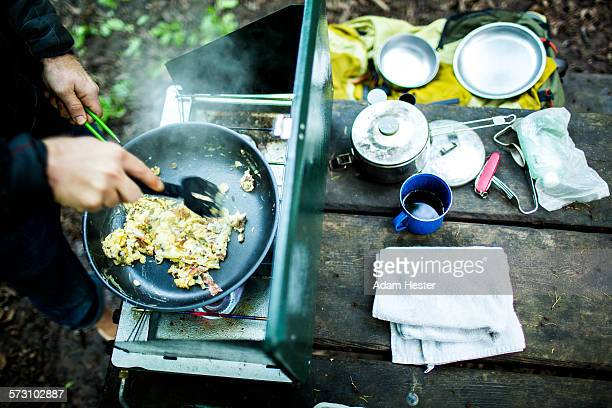 Caucasian man cooking eggs at campsite