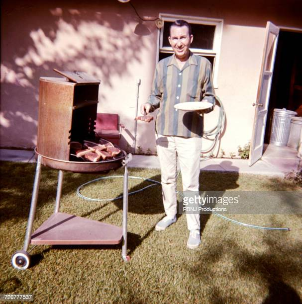 caucasian man cooking meat on barbecue in yard - filme de arquivo - fotografias e filmes do acervo
