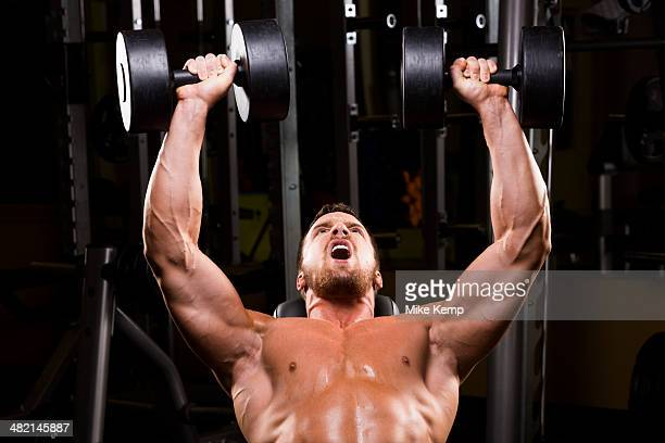 Caucasian man doing incline chest presses with dumbbells in gym