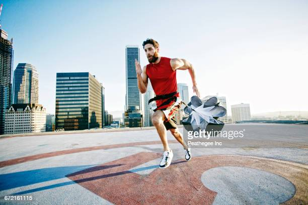 Caucasian man doing resistance training with parachute on rooftop