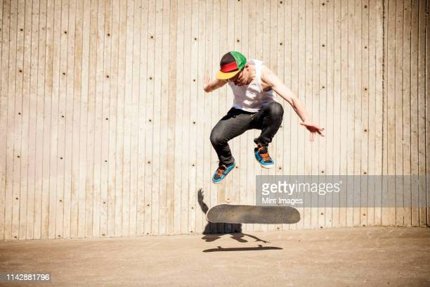 caucasian man doing skate trick near wooden wall - sport venue stock pictures, royalty-free photos & images