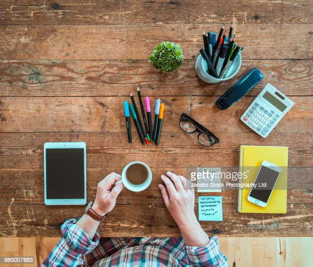 caucasian man drinking coffee at wooden table with pens and technology - list stock pictures, royalty-free photos & images