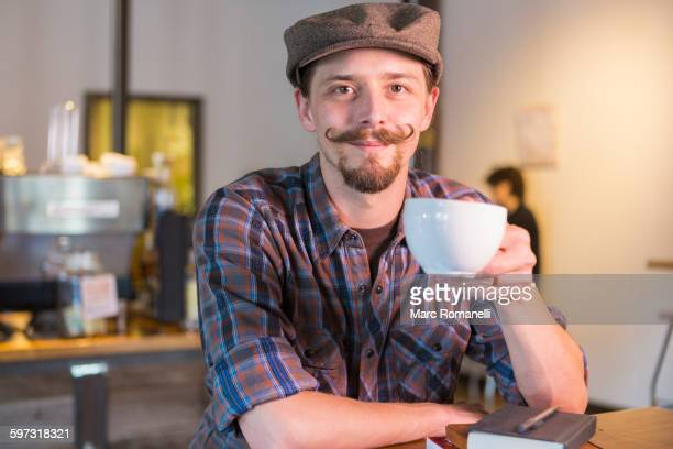caucasian man drinking coffee in cafe - mustache stock pictures, royalty-free photos & images