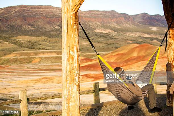 Caucasian man drinking coffee in hammock, Painted Hills, Oregon, United States