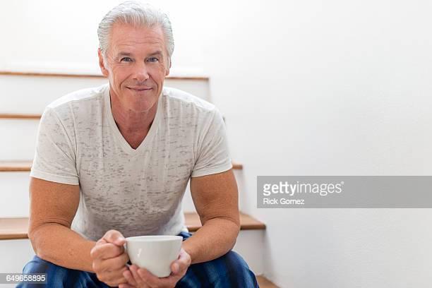 Caucasian man drinking coffee on stairs
