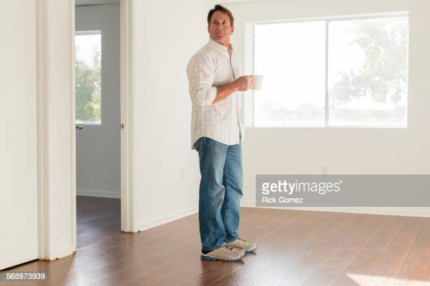 Caucasian man drinking cup of coffee in empty room
