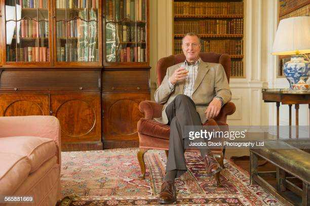caucasian man drinking in ornate library - england stock-fotos und bilder