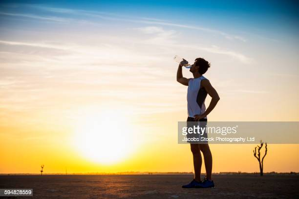 caucasian man drinking water bottle in desert - thirsty stock pictures, royalty-free photos & images