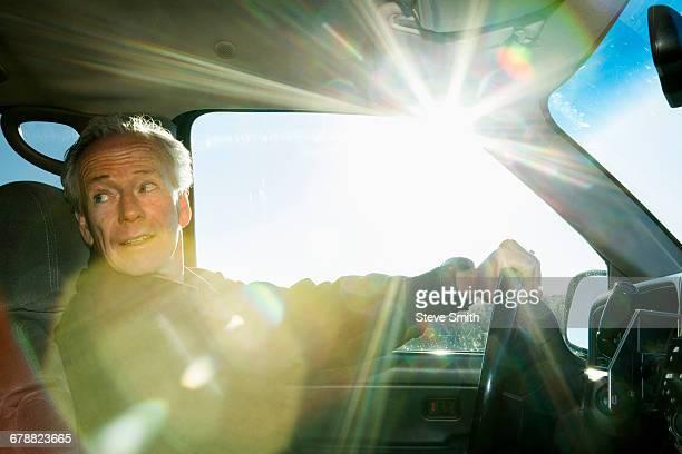 Caucasian man driving car looking back