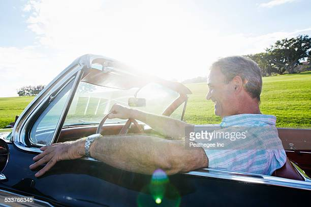 caucasian man driving classic convertible - convertible stock photos and pictures