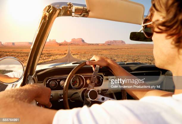 Caucasian man driving convertible on remote road