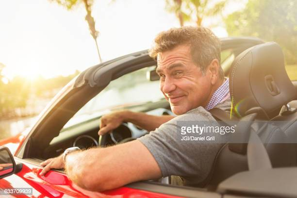 Caucasian man driving convertible