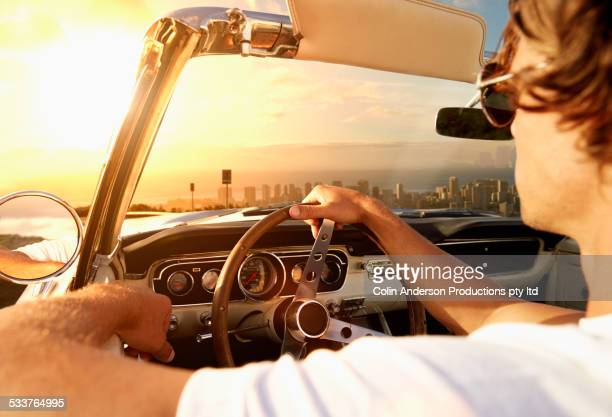 Caucasian man driving convertible towards cityscape