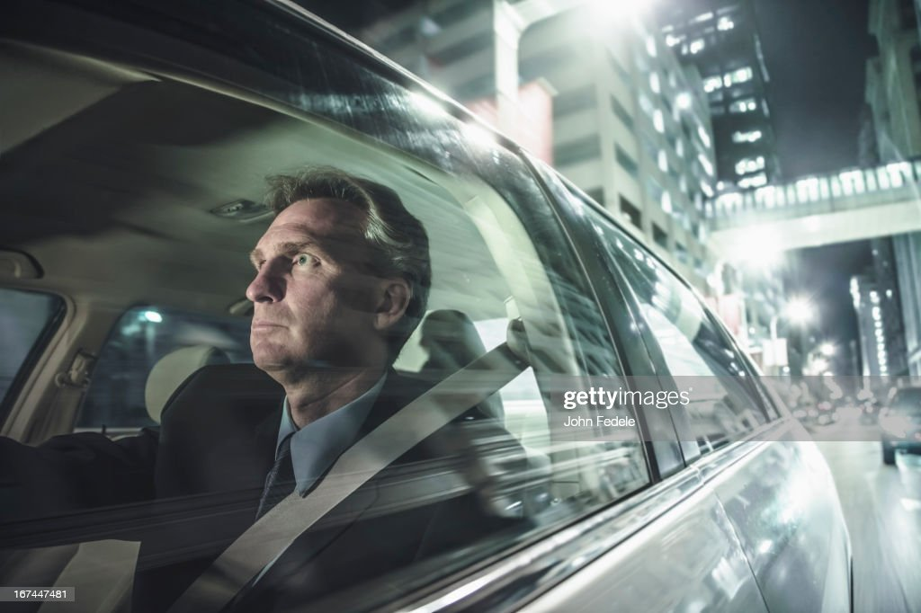 Caucasian man driving on city street : Stock Photo