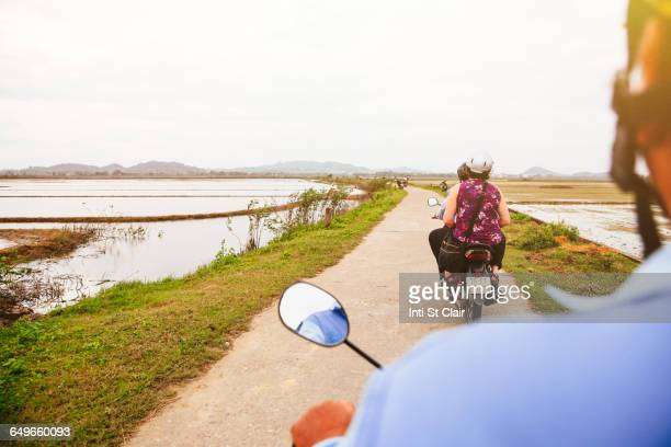 Caucasian man driving scooter in rural landscape