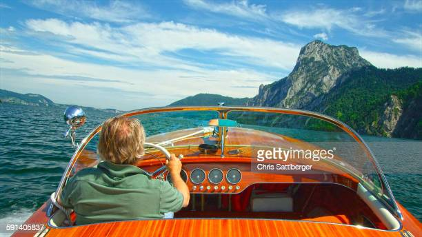 Caucasian man driving speedboat on remote lake