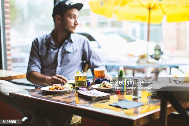 Caucasian man eating tacos in restaurant