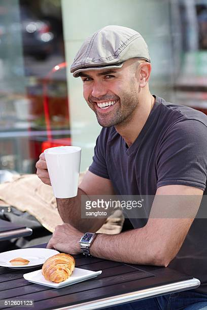 Caucasian man enjoying a cup of coffee at cafe smiling