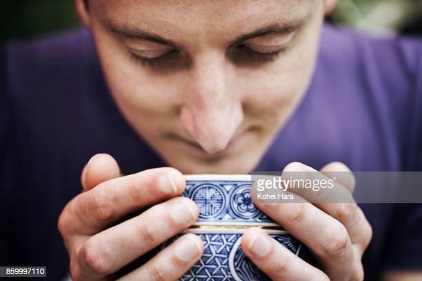 Caucasian man enjoying Japanese powdered green tea in the Japanese garden