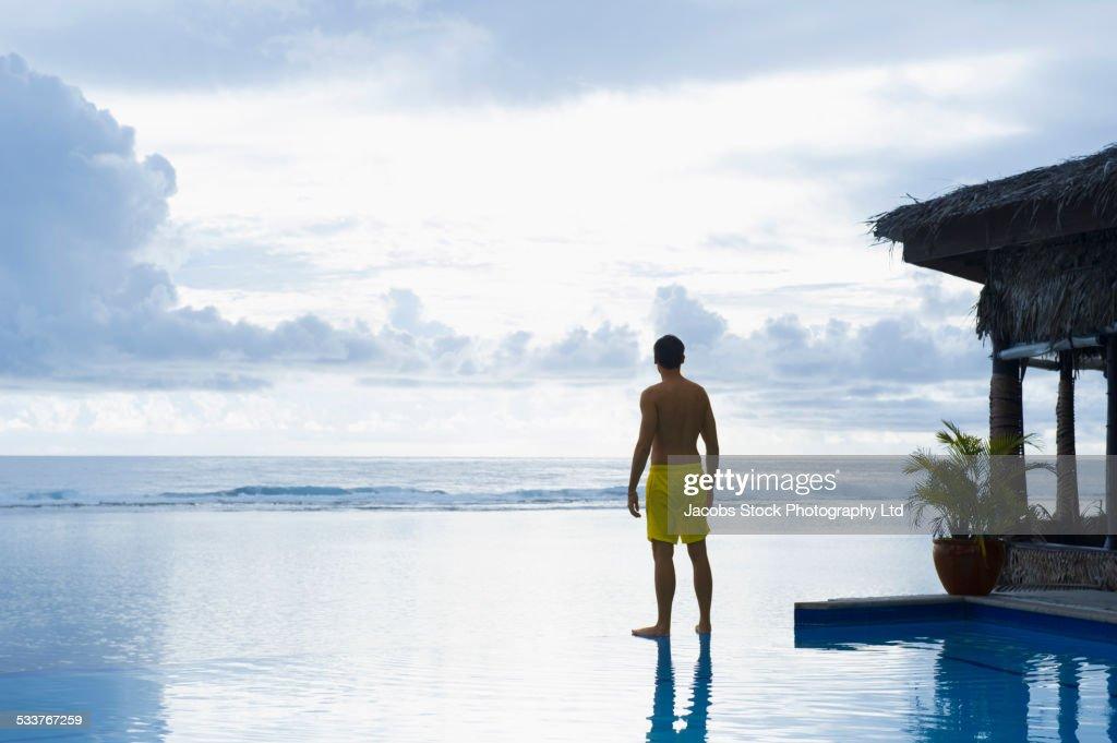 Caucasian man enjoying view from swimming pool : Foto stock