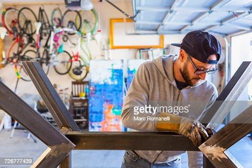 Caucasian man examining metal sculpture