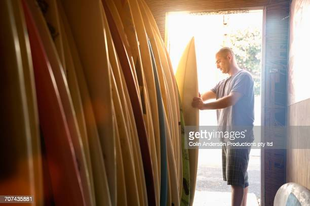 Caucasian man examining surfboard in shop