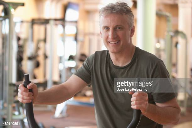 Caucasian man exercising in gym