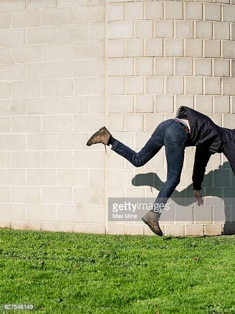 Caucasian man falling near brick wall