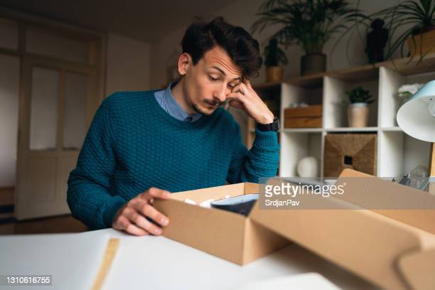 uomo caucasico che si sente deluso dopo aver disimballato un pacco con l'ordine sbagliato a casa - delusione foto e immagini stock