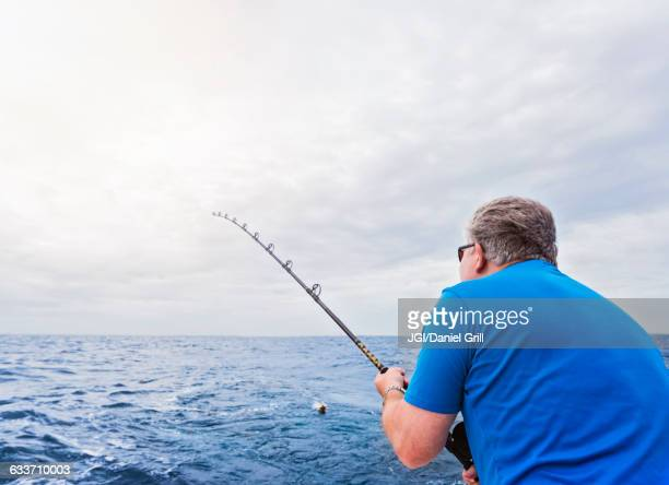 caucasian man fishing in ocean - deep sea fishing stock photos and pictures