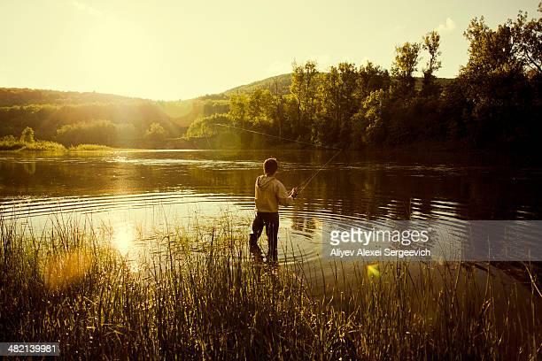 caucasian man fishing in still lake - angeln stock-fotos und bilder