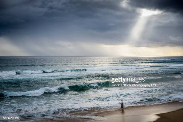 Caucasian man fishing in stormy waves on beach
