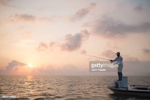 Caucasian man fishing on boat in ocean