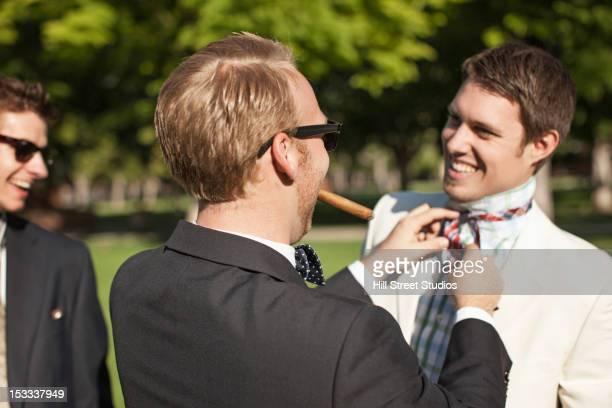 caucasian man fixing friend's tie - caldwell idaho foto e immagini stock