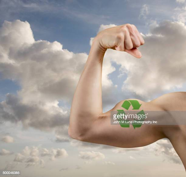 Caucasian man flexing biceps with recycle symbol