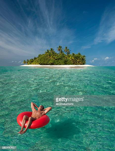 Caucasian man floating near tropical island