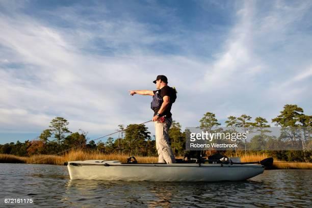 Caucasian man fly fishing in kayak on river