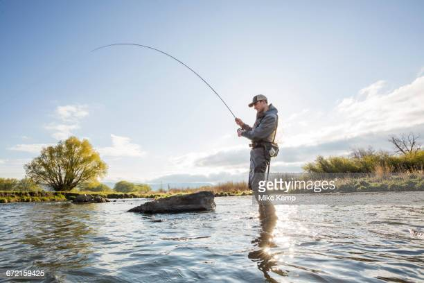 caucasian man fly fishing in river - fly fishing stock photos and pictures